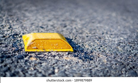 Yellow plastic heavy duty road stud in the middle of the road