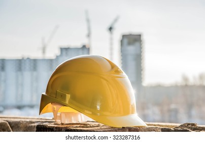 yellow plastic helmet for workers security lie on windowsill  of window frame against multistories house with construction crane at evening light background Copy space for inscription or objects