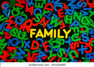 Yellow plastic letters word FAMILY among colorful plastic letters on black background , family concept