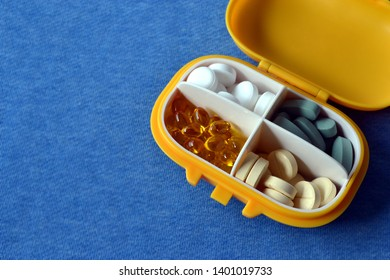 Yellow plastic medicament container with pills on blue background. Copy space
