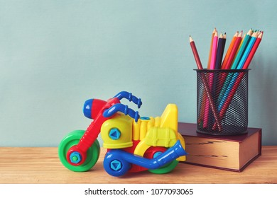 Yellow plastic motorbike toy, book and colorful pencils on wooden table