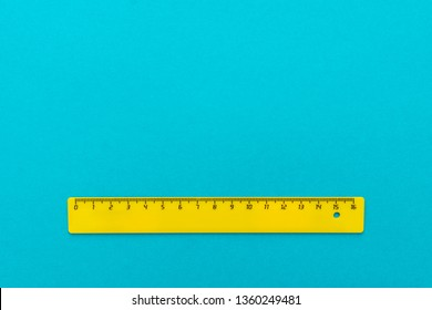 yellow plastic ruler on the turquoise blue background