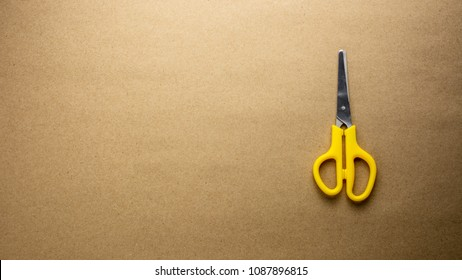 yellow plastic scissors on craft recycled paper - background