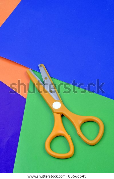 yellow plastic scissors oncolored papers