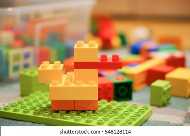 Yellow plastic toy duck made of Lego Duplo blocks lying on a floor in soft focus on December 2016 in Poznan, Poland