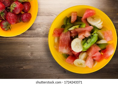 yellow plate of healthy fresh fruit salad on brown  wooden background . fruit salad top view