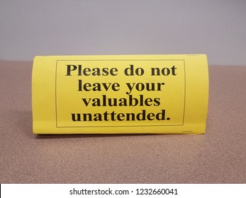yellow please do not leave your valuables unattended sign on table