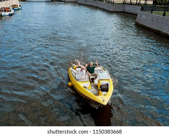A yellow pleasure boat sails along the Neva River against the backdrop of St. Petersburg, Russia.