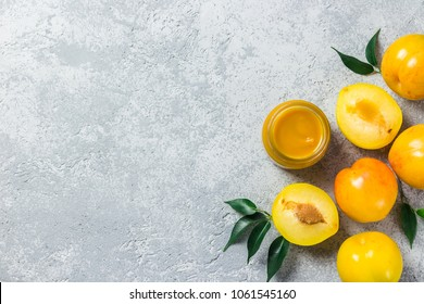 Yellow plum sauce in glass jar and fresh golden plums on concrete background. Top view, space for text.