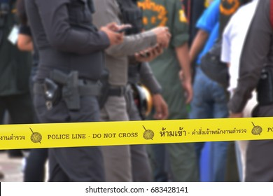 The yellow police tape, with the text: police line do not cross. and Thailand language text with meaning: do not go into the area as police commands.  Police thai and rescuers blur image