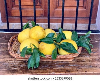 Yellow pomelo fruits with green leaves in the basket on vintage wooden table as table decoration