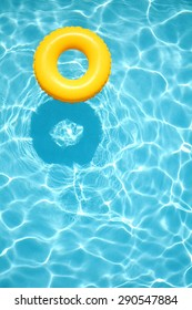 Yellow pool float, ring floating in a refreshing blue swimming pool