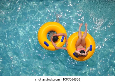 yellow pool floats in a fleshing blue swimming pool.