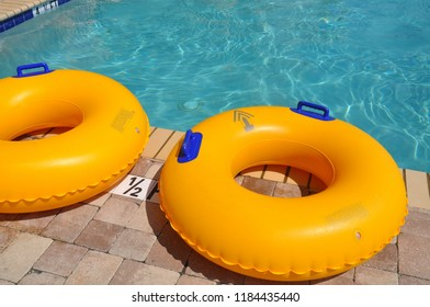 Yellow pool floats on edge of swimming pool.