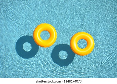yellow pool floats in a refreshing cool blue swimming pool