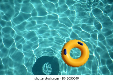 Yellow pool ring floating in a refreshing cool blue swimming pool.