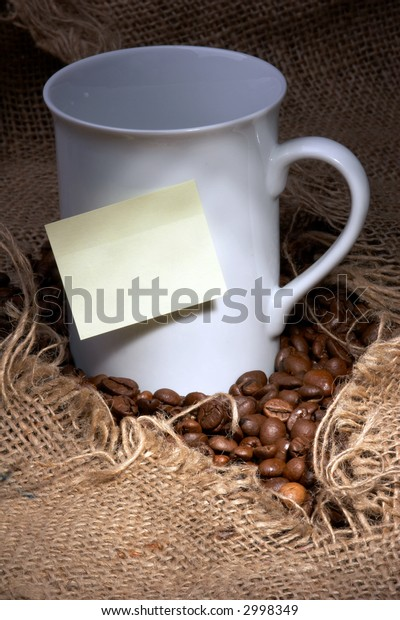 yellow post-it on white coffee cup - burlap sack and coffee beans as background