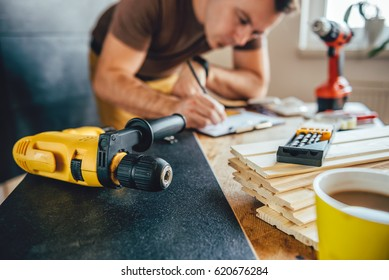 Yellow power drill and man making draft plan using pencil on the table with tools in the background