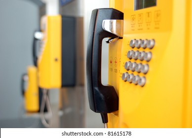yellow public telephones with emergency icons