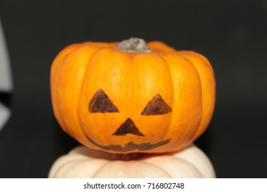 Yellow pumpkin in white in the hands of Halloween