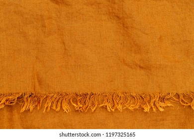 Yellow pure linen texture. Wrinkled linen fabric background. Natural linen yellow bedspread with fringe