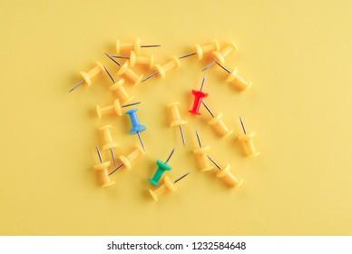 Yellow pushpins on yellow background.