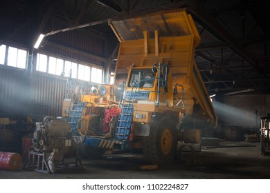 Yellow quarry dump truck in service zone