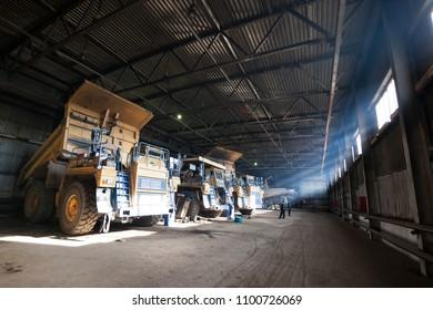 Yellow quarry dump trucks in service zone