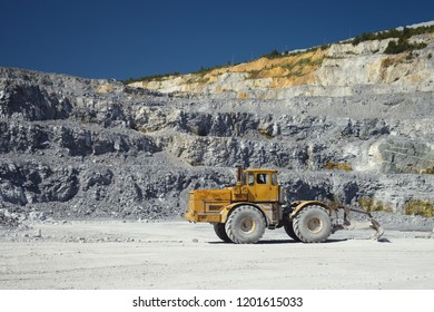 Yellow quarry tractor with scraper in a lime pit in sunny weather, close-up.