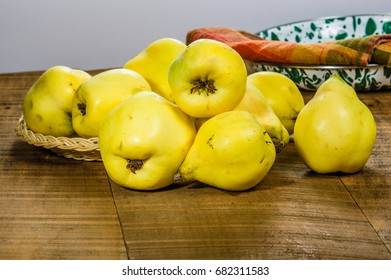 Yellow quince fruit in wicker tray on table