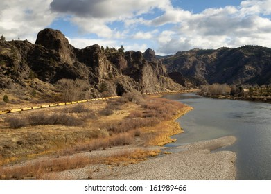 Yellow railroad rail-cars sit in a low river bend in the Rocky Mountains Northwestern United States