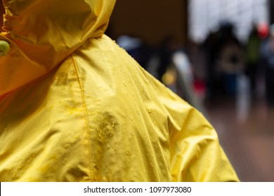 Yellow raincoat rain jacket. Selective focus on raindrops on waterproof or water resistant coat with hood.