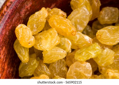 Yellow raisins close-up in a brown wooden bowl