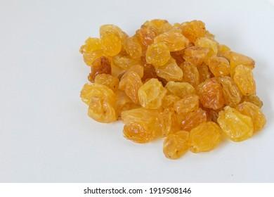 Yellow raisins on white background,