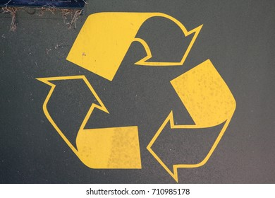 Yellow recycling symbol on metal surface