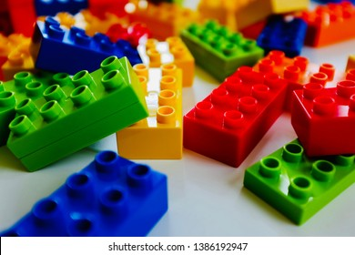 Yellow, red, blue, and green plastic building blocks for kids isolated on white.