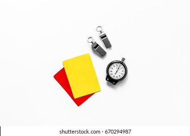 Yellow and red cards, stopwatch, whistle on white background top view copyspace