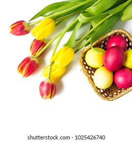 Yellow and red colored easter eggs and  bouquet of tulips on white background.