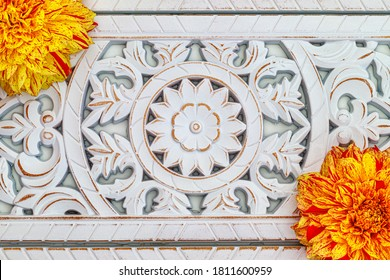 Yellow red dahlia flowers on white table, top view. White Stunning Carved Distressed Mango wood. Oriental Carved Floral Glory Decor.