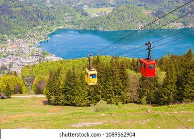 Yellow and red gondolas of Zwoelferhorn Seilbahn (cable way) travel up and down alpine peak with a view of village St.Gilgen and Wolfgangsee lake, Salzburg land, Austria