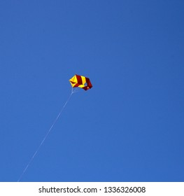 yellow and red kite flying on line against deep blue sky