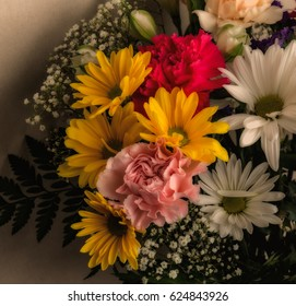 Yellow and red muted flowers against a cream burlap background