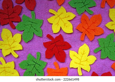 Yellow, red, orange and green Maple leaves out of felt on fabric as a background