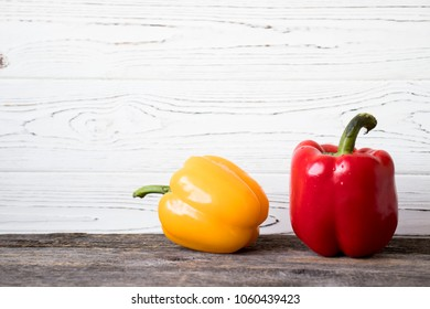 yellow and red pepper on wooden background