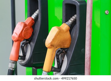 yellow and red petrol gas pump nozzles in a service station background green,Fuel nozzle in oil station Thailand