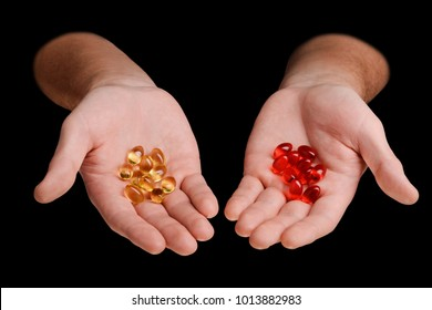 Yellow and red pills on hands. Softgel vitamins and minerals, Medication course and healthcare concept.