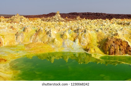 Yellow and red rocks over a green lake at the hot sulfur springs in the danakil depression in dallol ethiopia
