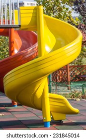 Yellow and red round slides in bright sunlight on soft surface playground.