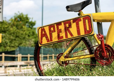 Yellow and red sign with text Aperto (open in italian language), hanging from an old bicycle colored in bright colors on green grass