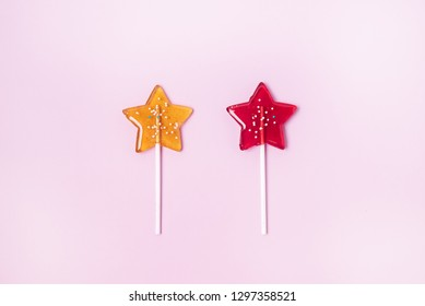 Yellow and Red Stars Shaped Lollipop on Light Pink Background Homemade Fruit Lollipop Candy Background Flat Lay Top View Copy Space